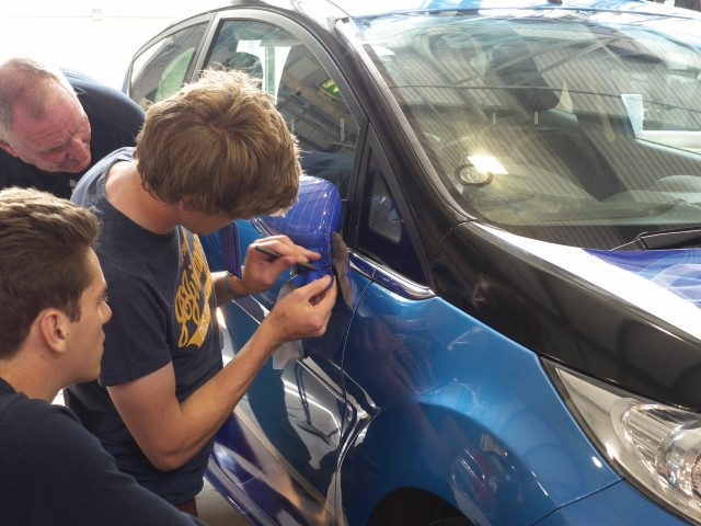 Oxford Brookes students wrapping a wing mirror
